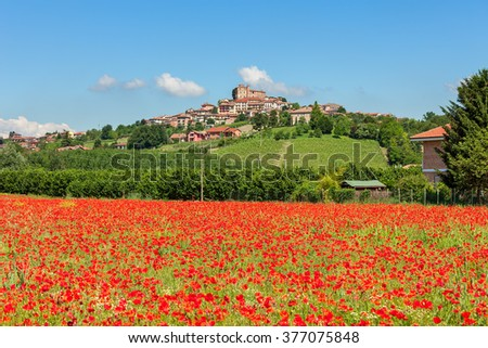 Rural field of red poppies under blue sky as small town on the hill on background in Piedmont, Northern Italy. - stock photo