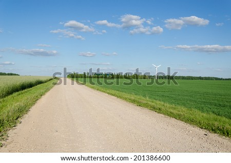 Rural gravel road between agriculture fields and wind mill windmill rorate generating alternative renewable electricity energy.  - stock photo