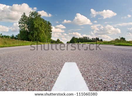 Rural grey road on sunny summer day - stock photo