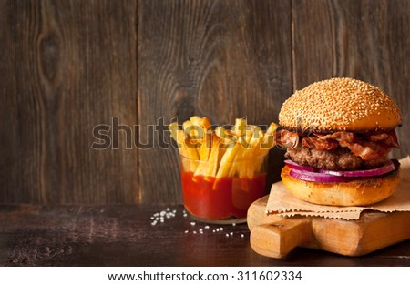 Rural hamburger and fried potatoes with tomato sauce. - stock photo