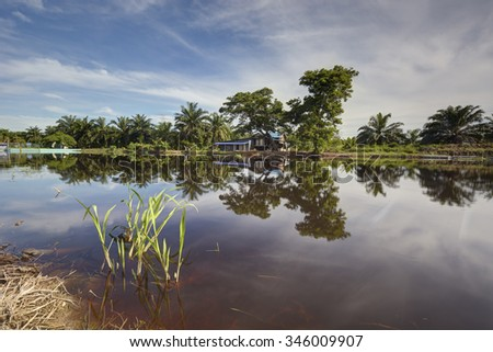 Rural house with river reflection during daytime.