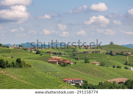 Rural houses, green hills and vineyards of Piedmont, Northern Italy. - stock photo