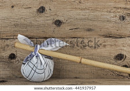 Rural knapsack on a bamboo pole on a old wooden background