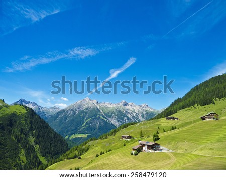 rural landscape and alpine village with farm houses - stock photo