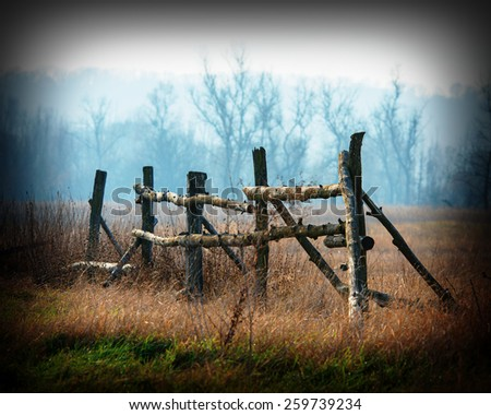 Rural landscape autumn trees and old wooden fence on the background of trees - stock photo