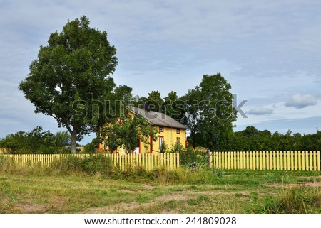 Rural landscape. Cozy yellow house next to field - stock photo