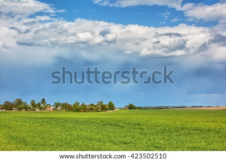 Rural landscape - meadows, village with thunderclouds over them. - stock photo