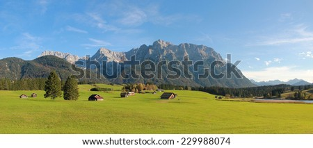 rural landscape near mittenwald, farmland with huts against karwendel mountains - stock photo
