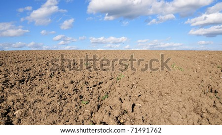 Rural Landscape of Bare Earth with a Beautiful Blue Cloudy Sky Above - stock photo
