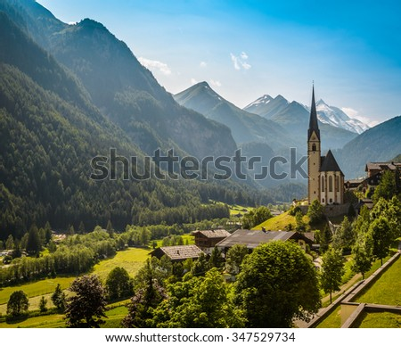 Rural landscape of Heiligenblut with St Vincent Church in Carynthia and Grossglockner (3797 m. elevation) highest mountain from Austria in background. - stock photo