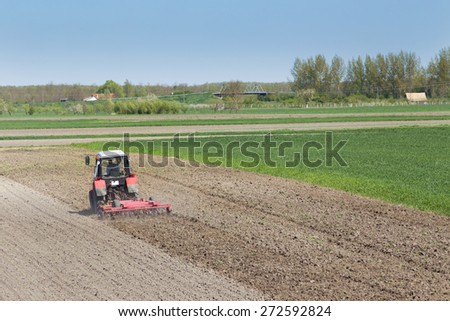 Rural landscape of tractor plowing fertile land near the village - stock photo