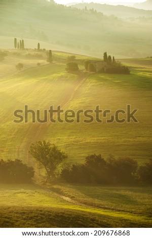 Rural landscape of Tuscany on a hazy sunny morning - stock photo
