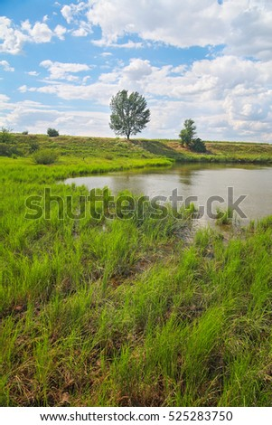 Rural landscape, river coast Ingulets against the sky with clouds