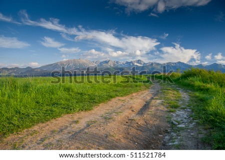 Rural landscape - road, green fields and mountains on the background - The Tatra Mountains, Poland