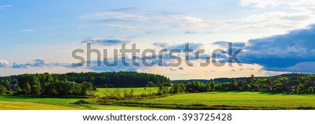 Rural landscape. Sunny summer evening. Sky with clouds, grass field, trees and farmhouses. Panoramic shot. Toned image. - stock photo
