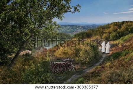 Rural landscape. Two nuns walk along the village path