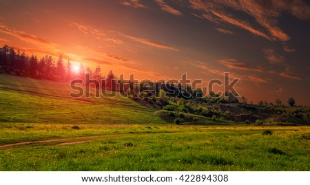 Rural landscape with a hill. Green meadow under sunset, colorful sky with clouds Dramatic morning scene. Beautiful natural landscape - stock photo