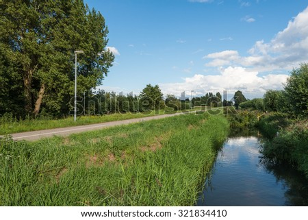Rural landscape with a straight asphalt road with a small ditch, trees and lampposts on the sides of the road. - stock photo