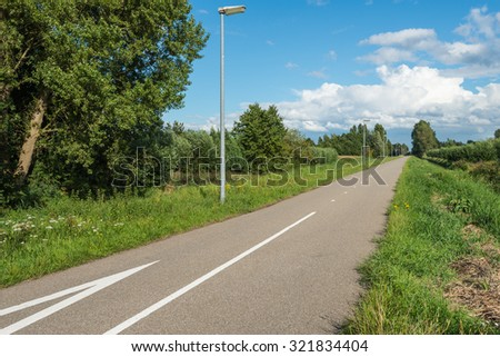 Rural landscape with a straight asphalt road with trees and lampposts on the side of the road. - stock photo