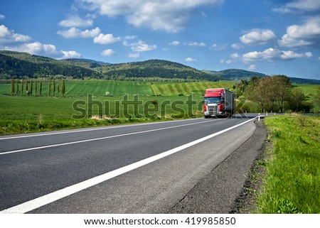 Rural landscape with asphalt road and oncoming red truck. Green fields and wooded mountains in the background. Sunny spring day with blue skies and white clouds. - stock photo