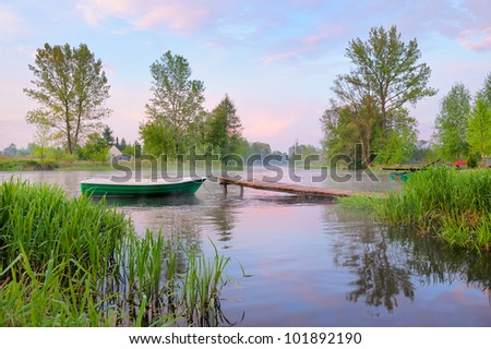 Rural landscape with boat and footbridge on the Narew river after fog, Poland. - stock photo