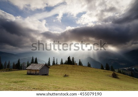 Rural landscape with dramatic sky. Autumn in the mountain village. Wooden cottage in the meadow. Storm clouds and sun rays. Carpathians, Ukraine, Europe - stock photo