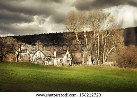 Rural landscape with houses lit in a moody way through a cloudy sky - stock photo