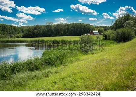 Rural landscape with  lake, pasture and farm's barn framed by trees