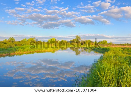 Rural landscape with Narew river and Stratocumulus clouds. - stock photo