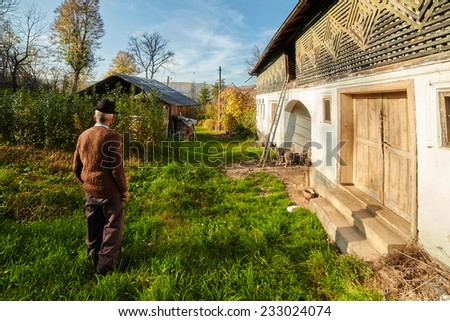 Rural landscape with old farmer standing near his house and his dog - stock photo