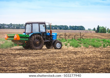 Rural landscape with old tractor in a field sow seed in the plowed soil.