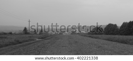 Rural landscape with road and houses. Village road in the fog. Morning mist. Road, fog, village. Black & white photo - stock photo