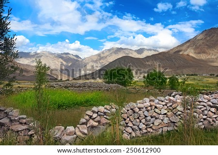 Rural landscape with stone wall and valley in Himalayas mountains - stock photo