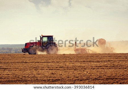 Rural landscape with  tractor in the field during sowing grain - stock photo