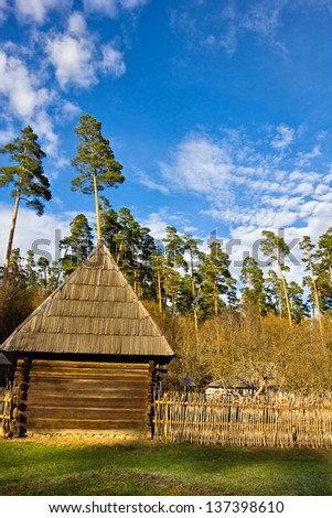 Rural landscape with wooden house and fence against blue sky