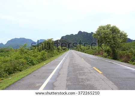 Rural lanes running toward the mountains in the morning, a pale blue color. - stock photo