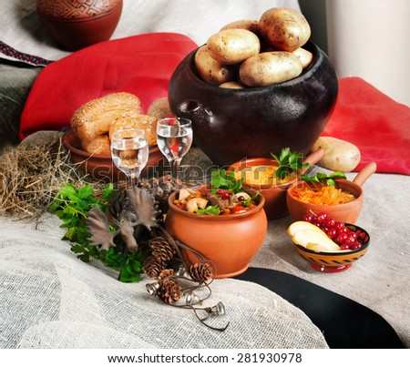 rural life with the pot, stew pot, potatoes, elk, pottery and glass of vodka - stock photo