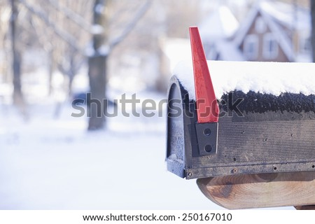 Rural mailbox postbox letterbox in snow with red flag up selective focus blurred background copy space. Concepts: Moving, new home, you have got mail, contact us, winter weather snowstorm blizzard.  - stock photo