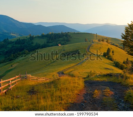 Rural mountain landscape hills with road in scenic sunset light.