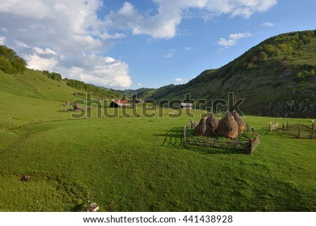 Rural mountain landscape with haystacks against cloudy sky.