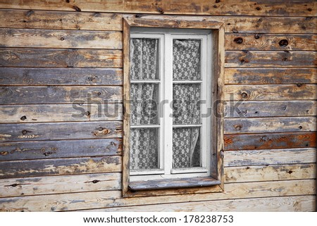 Rural much neglected window in wooden wall of house, wooden background