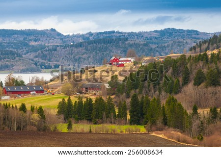 Rural Norwegian landscape with red wooden houses on hills - stock photo