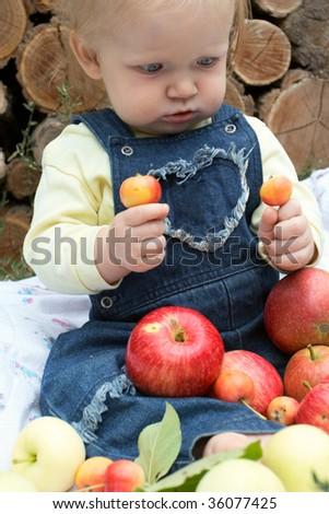 rural picnic scene. Child with the apple is sitting on a grass and firewood wall at the background