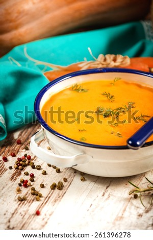 Rural pumpkin soup on rustic wood table - stock photo