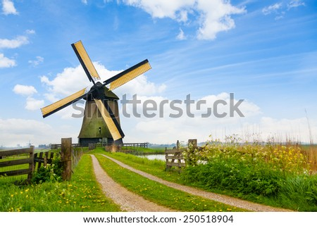 Rural road and windmill in Netherlands  - stock photo
