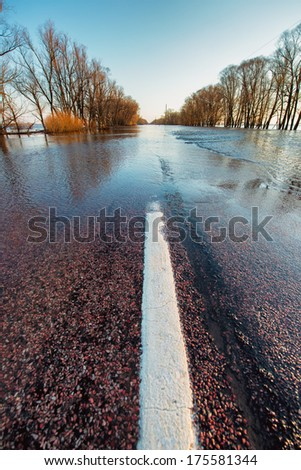 Rural road covered by hight water during spring flood. - stock photo