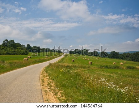 Rural road crossing a field with scattered straw bales after harvest in the Summertime - stock photo