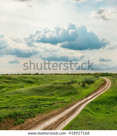 rural road in green meadow and dramatic sky over it
