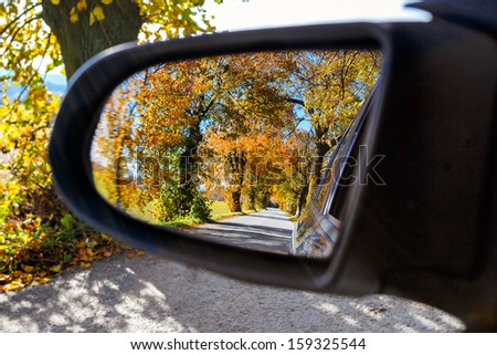 rural road in the autumn with yellow colored trees reflected in car mirror - stock photo