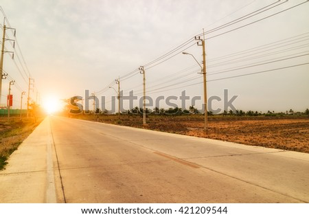 Rural road in the sunset - stock photo